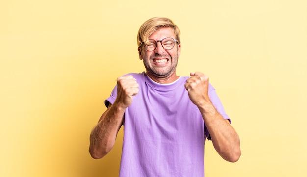 Hübscher blonder erwachsener mann, der triumphierend schreit, lacht und sich glücklich und aufgeregt fühlt, während er den erfolg feiert