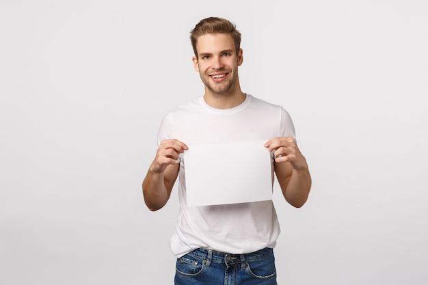 Hübscher blonder kerl mit blauen augen und dem weißen t-shirt, das papier hält