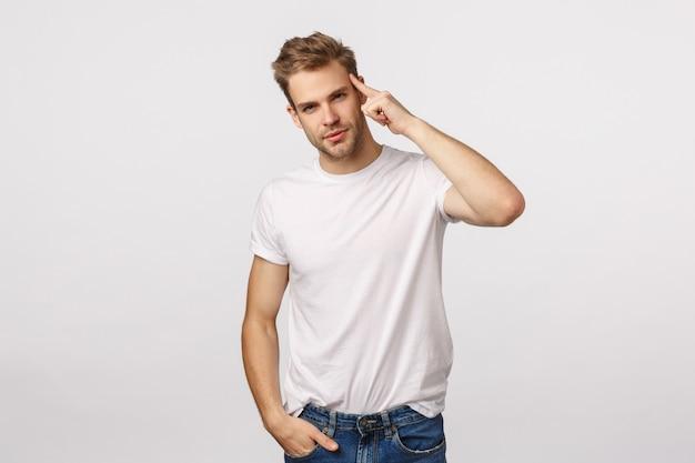 Hübscher blonder kerl mit blauen augen und weißem t-shirt denken