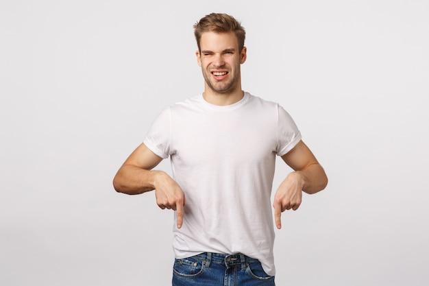 Hübscher blonder kerl mit blauen augen und weißem t-shirt unten zeigend