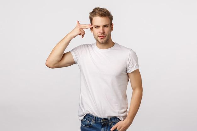 Hübscher blonder kerl mit blauen augen zeigend auf seinen kopf