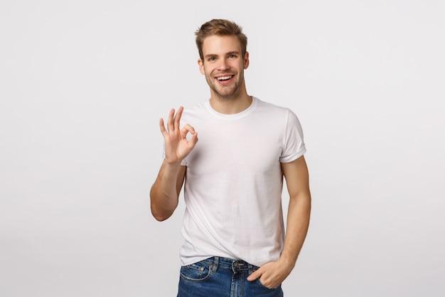 Hübscher blonder kerl mit den blauen augen, die zustimmungszeichen geben