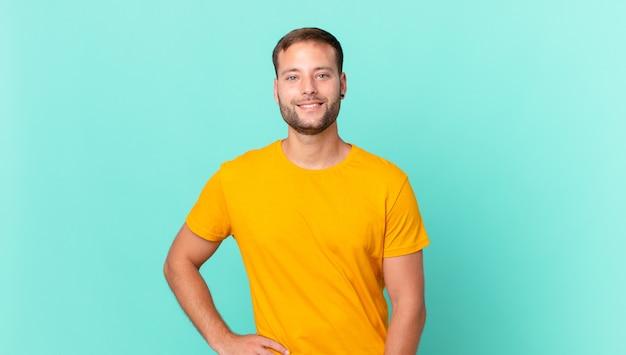 Hübscher blonder mann, der glücklich mit einer hand auf der hüfte und selbstbewusst lächelt