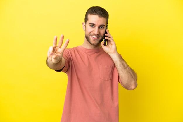 Hübscher blonder mann, der handy über isoliertem hintergrund glücklich und drei mit den fingern zählend verwendet