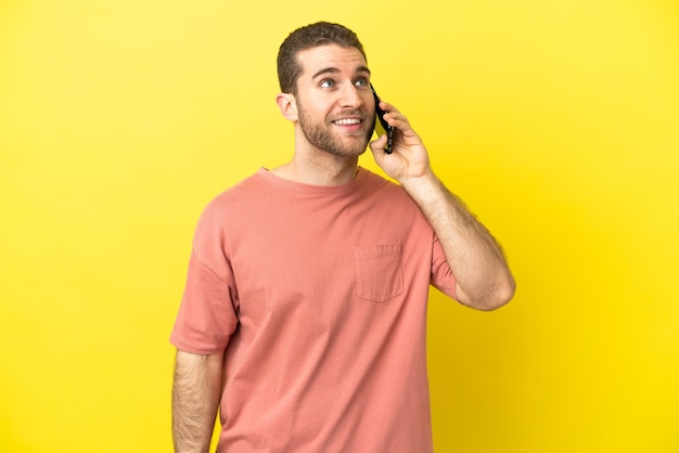 Hübscher blonder mann, der handy über isoliertem hintergrund verwendet, der eine idee beim nachschlagen denkt