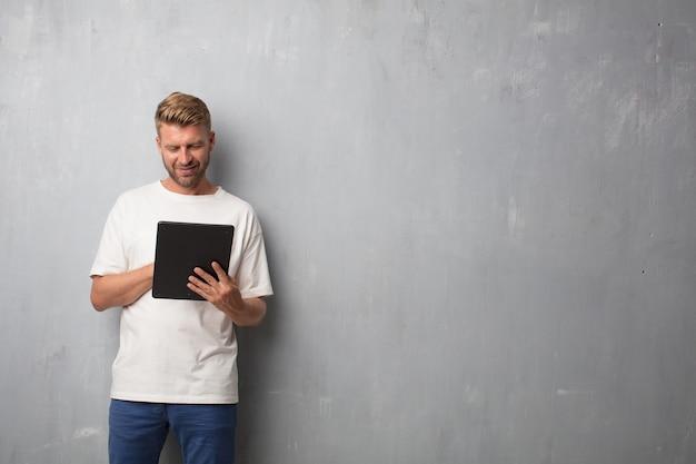 Hübscher blonder mann, der zu einer tablettenauflage über einer schmutzwand schaut