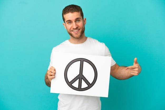 Hübscher blonder mann isoliert, der ein plakat mit friedenssymbol hält und darauf zeigt