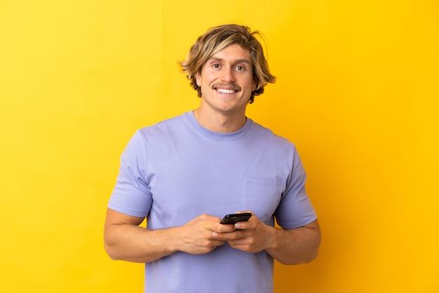 Hübscher blonder mann isoliert, der eine nachricht mit dem handy sendet