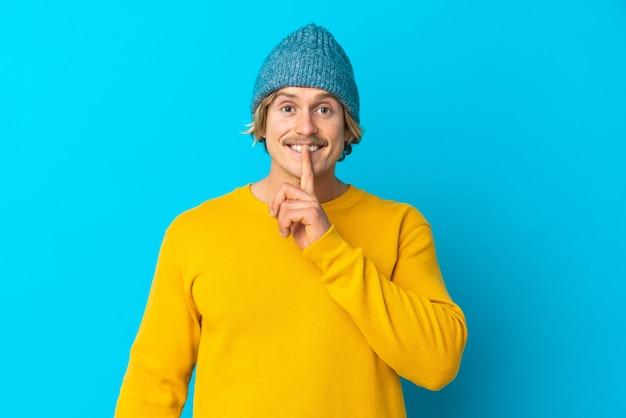 Hübscher blonder mann lokalisiert auf blauer wand, die ein zeichen der stille geste zeigt finger in den mund setzen