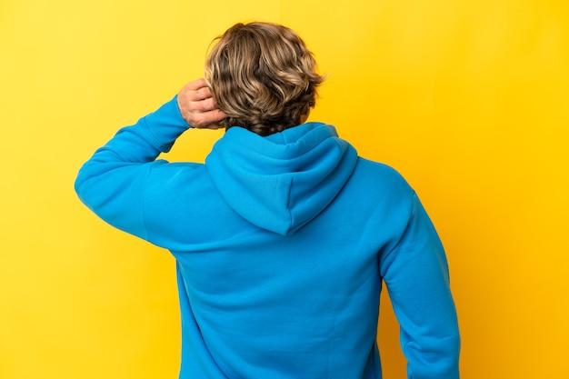 Hübscher blonder mann lokalisiert auf gelb in der hinteren position und im denken