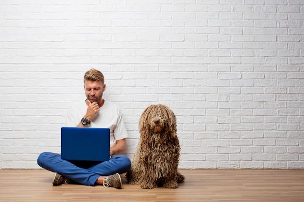 Hübscher blonder mann mit einem hund und einem tragbaren computer