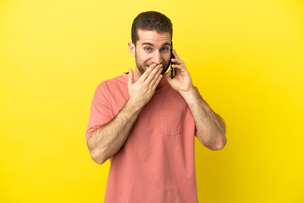 Hübscher blonder mann mit handy über isoliertem hintergrund glücklich und lächelnd, der den mund mit der hand bedeckt