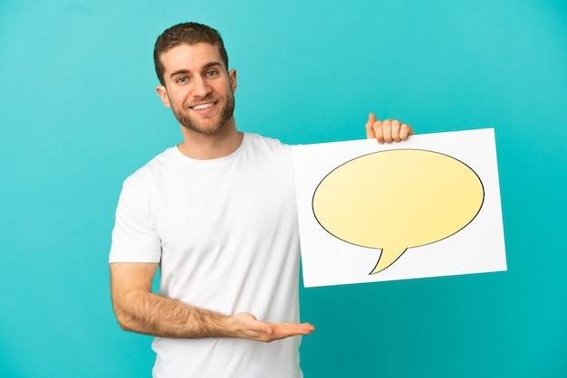 Hübscher blonder mann über isoliert, der ein plakat mit sprechblasensymbol hält und darauf zeigt