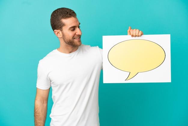Hübscher blonder mann über isoliert, der ein plakat mit sprechblasensymbol hält