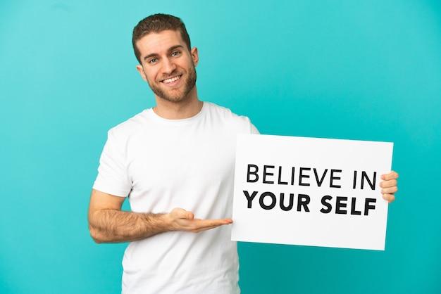 Hübscher blonder mann über isoliertem blauem hintergrund, der ein plakat mit dem text believe in your self hält und darauf zeigt