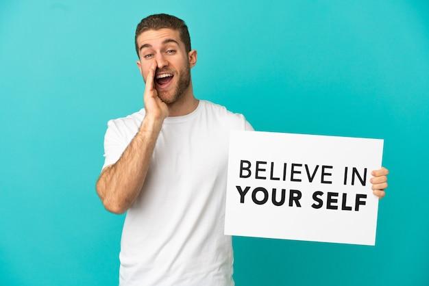Hübscher blonder mann über isoliertem blauem hintergrund, der ein plakat mit dem text believe in your self hält und schreit