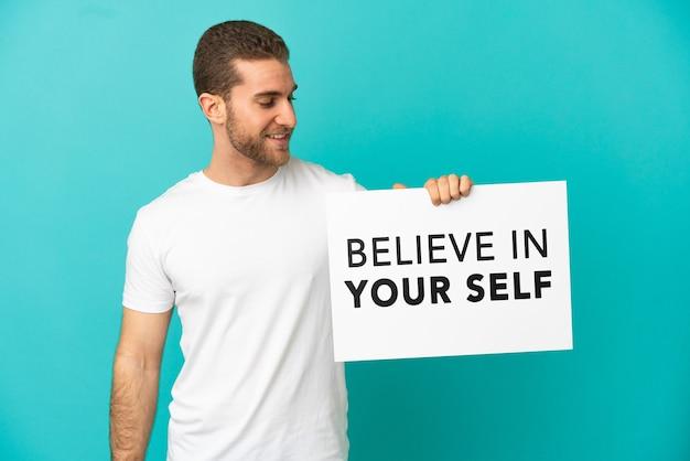 Hübscher blonder mann über isoliertem blauem hintergrund, der ein plakat mit dem text believe in your self hält