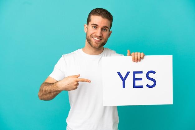 Hübscher blonder mann über isoliertem blauem hintergrund, der ein plakat mit dem text ja hält und darauf zeigt
