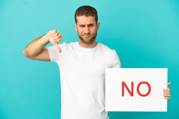Hübscher blonder mann über isoliertem blauem hintergrund, der ein plakat mit dem text nein hält