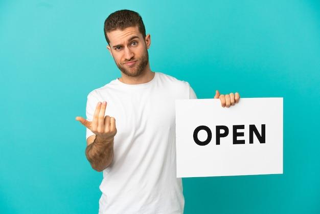 Hübscher blonder mann über isoliertem blauem hintergrund, der ein plakat mit dem text open hält und kommende geste macht