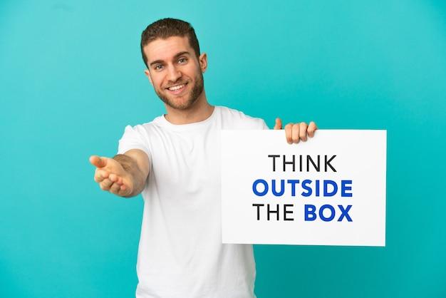 Hübscher blonder mann über isoliertem blauem hintergrund, der ein plakat mit dem text think outside the box hält, um einen deal zu machen
