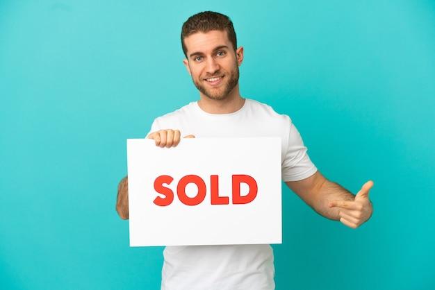 Hübscher blonder mann über isoliertem blauem hintergrund, der ein plakat mit dem text verkauft hält und darauf zeigt