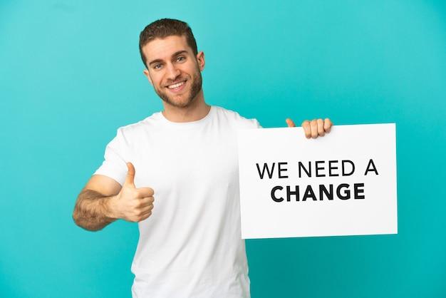 Hübscher blonder mann über isoliertem blauem hintergrund, der ein plakat mit dem text we need a change mit daumen nach oben hält