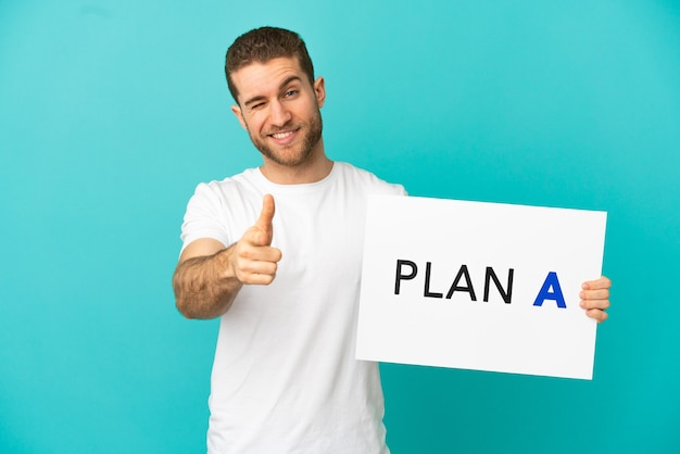 Hübscher blonder mann über isoliertem blauem hintergrund, der ein plakat mit der nachricht plan a hält und nach vorne zeigt