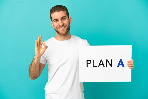 Hübscher blonder mann über isoliertem blauem hintergrund, der ein plakat mit der nachricht plan a mit ok-zeichen hält