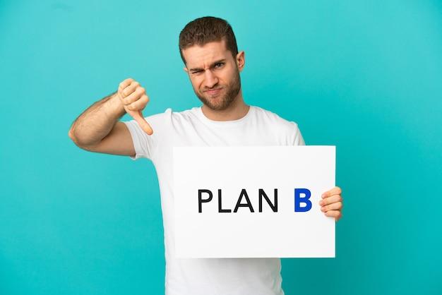 Hübscher blonder mann über isoliertem blauem hintergrund, der ein plakat mit der nachricht plan b hält und ein schlechtes signal macht