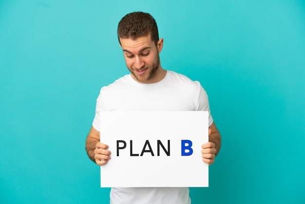 Hübscher blonder mann über isoliertem blauem hintergrund, der ein plakat mit der nachricht plan b hält