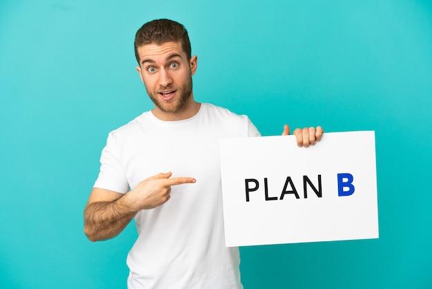 Hübscher blonder mann über isoliertem blauem hintergrund, der ein plakat mit der nachricht plan b mit überraschtem ausdruck hält