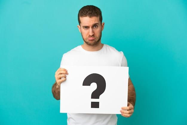 Hübscher blonder mann über isoliertem blauem hintergrund, der ein plakat mit fragezeichensymbol mit traurigem ausdruck hält