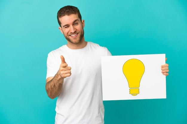 Hübscher blonder mann über isoliertem blauem hintergrund, der ein plakat mit glühbirnensymbol hält und nach vorne zeigt