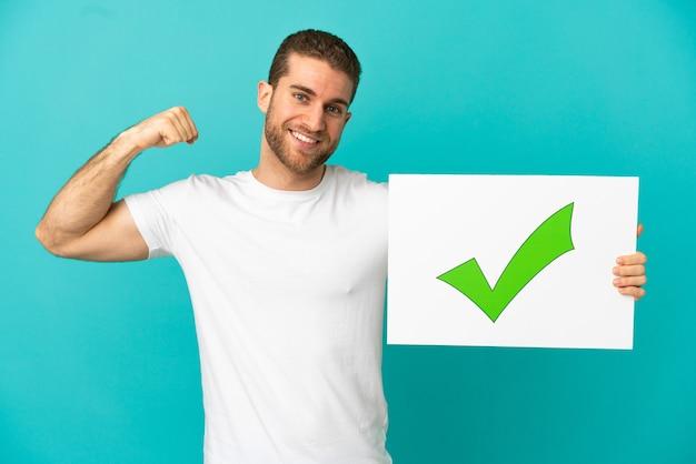 Hübscher blonder mann über isoliertem blauem hintergrund, der ein plakat mit grünem häkchen-symbol hält und starke geste macht