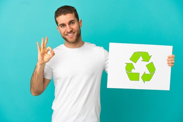 Hübscher blonder mann über isoliertem blauem hintergrund, der ein plakat mit recycling-symbol hält und einen sieg feiert