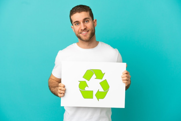 Hübscher blonder mann über isoliertem blauem hintergrund, der ein plakat mit recycling-symbol mit glücklichem ausdruck hält