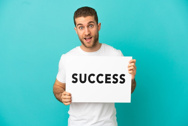 Hübscher blonder mann über isoliertem blauem hintergrund, der ein plakat mit text erfolg mit überraschtem ausdruck hält