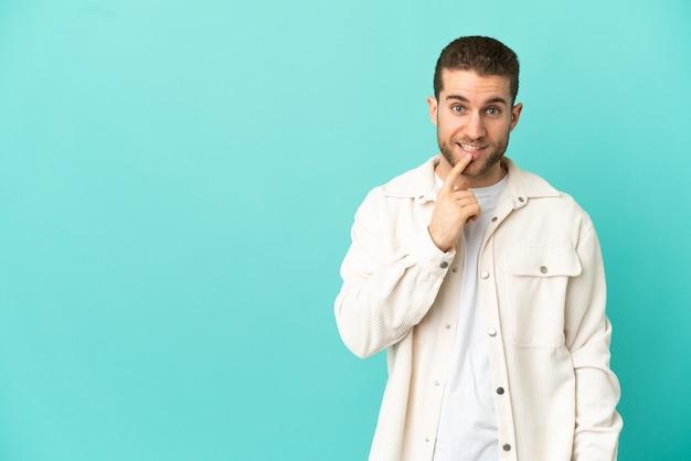 Hübscher blonder mann über isoliertem blauem hintergrund, der ein zeichen der stille zeigt, geste, die finger in den mund steckt
