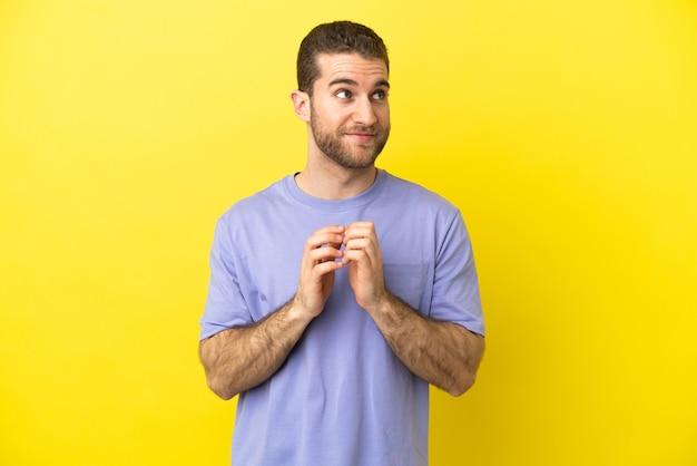 Hübscher blonder mann über isoliertem gelbem hintergrund, der etwas plant