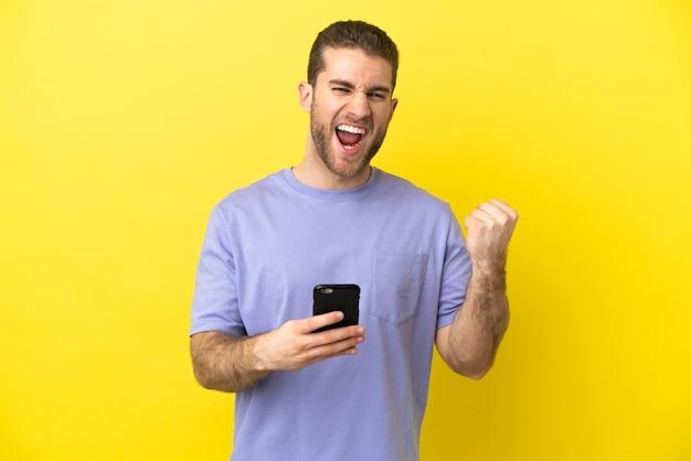 Hübscher blonder mann über isoliertem gelbem hintergrund mit telefon in siegesposition