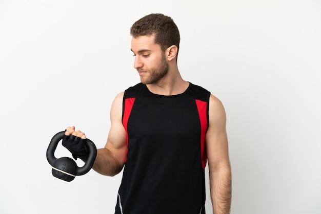 Hübscher blonder mann über isoliertem weißem hintergrund macht gewichtheben mit kettlebell