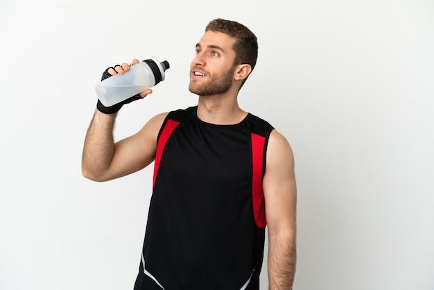 Hübscher blonder mann über isoliertem weißem hintergrund mit sportwasserflasche