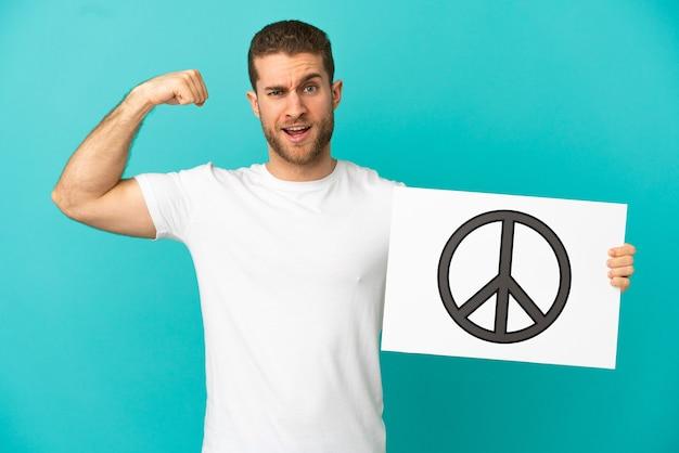 Hübscher blonder mann über isolierter blauer wand, die ein plakat mit friedenssymbol hält und starke geste tut
