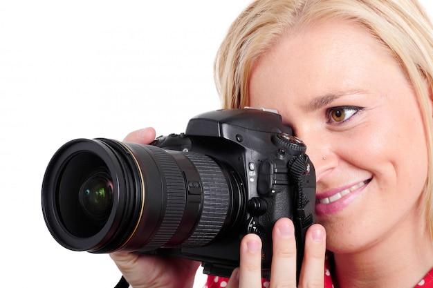 Hübscher blondinephotograph mit ihrer kamera, auf weiß
