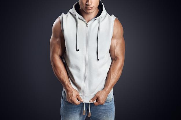 Hübscher bodybuilder, der grauen ärmellosen hoodie trägt