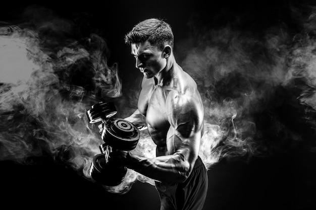 Hübscher bodybuilder, der übung mit dummkopf tut. rauch