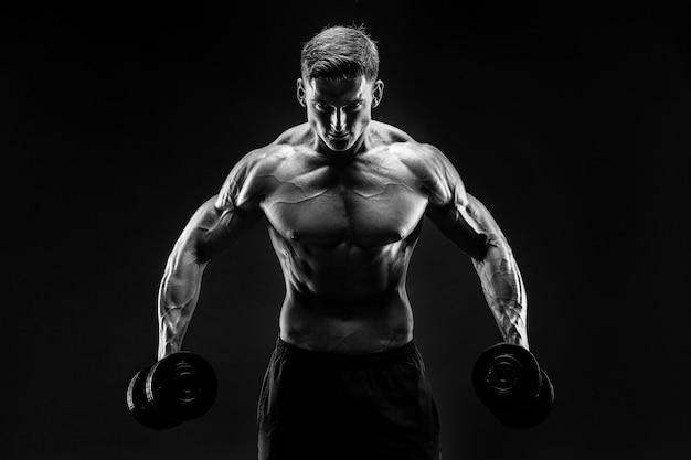 Hübscher bodybuilder, der übung mit dummkopf tut.