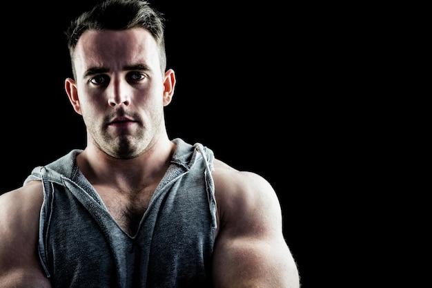 Hübscher bodybuilder mit den armen gekreuzt
