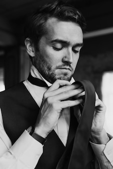 Hübscher bräutigam, der für hochzeits-zeremonie sich kleidet